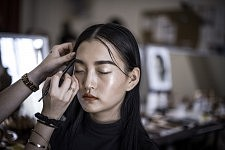 Model Cong He during making up before Ulyana Sergeenko's Haute-couture runway show. Le mannequin Cong He au maquillage avant le défilé Haute-couture de Ulyana Sergeenko.