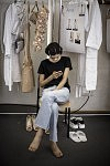 Model Aira Ferreira on her a phone in the fitting room before getting dressed for the Haute-Couture's runway show of Ulyana Sergeenko. Le mannequin Aira Ferreira sur son téléphone dans la salle d'essayage avant de mettre sa tenue de défilé Haute-Couture de Ulyana Sergeenko.