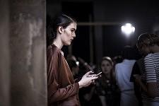 Model busy on her phone before the Ulyana Sergeenko's haute-couture runway show. Mannequin sur son téléphone avant le défilé haute-couture de Ulyana Sergeenko.