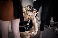 Harleth Kuusik crouched looking at her phone before Ulyana Sergeenko's haute-couture runway show. Harleth Kuusik accroupie avec son téléphone avant le défilé Haute-Couture de Ulyana Sergeenko.