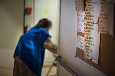 Old lady walking by the board of acronyms in a retirement home in Paris, september 2017.Vieille dame passant devant le tableau des acronymes dans un Ehpad à Paris, Septembre 2017.