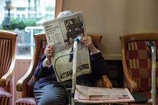 Lady reading the newspaper after the death of Liliane Bettencourt, in the living room of a retirement home, Paris, September 2017.