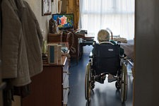 Lady in a wheelchair watching tv in her bedroom of a retirement home, Paris, September 2017.