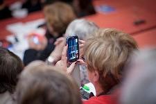 Woman looking l'image de Marisol Touraine in the screen of her cell phone in the Public, the ICCEC 2014, Ecole de Médecine, Paris. Femme regardant Marisol Touraine sur l'écran de son téléphone dans le public de l'ICCEC 2014, Ecole de médecine, Paris.