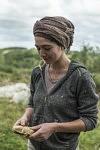 Elisa holding a piece of a dry mixture to feel texture and consistency of the clay-straw matter. Elisa tenant dans ses mains un morceau séché de terre-paille pour sentir la texture et la consistence de ce mélange de matière.