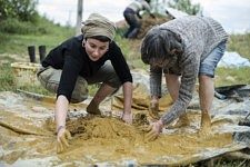 The first team of girls practising the mudding by stepping straw, clay and water inside the platic cover. La première équipe de filles piétinant dans la bâche le mélange terre-paille.