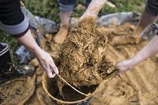 Détail sur les mains du groupe des femmes travaillant ensemble à produire le mélange terre-paille.
