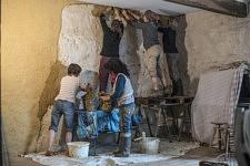 At the end of the afternoon, the girls start applying their straw-clay mixture on a wall of the collective building. A la fin de l'après-midi, les filles commencent à appliquer le mélange terre-paille sur le mur d'une pièce du bâtiment collectif.