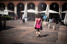 Young woman wearing a pink dress walking Place du Capitole, Toulouse, June 2017. Jeune femme en robe rose marchant Place du Capitole, Toulouse, Juin 2017.