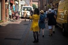 Young woman wearing a yellow dress walking in a street, Toulouse, June 2017. Jeune femme en robe jaune marchant dans la rue, Toulouse, Juin 2017.