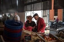 Clients choosing their products outside at the Victor Hugo Market.Clients choississant leurs produits en extérieur au Marché Victor Hugo.
