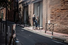 Two women talking in sunny street of the center of Toulouse.
