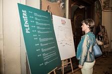 Femme devant le programme de la Plénière