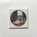 """""""Rue des trésors"""", pièce unique 10 x 10 cm, signée au dos, faite à la main par la photographe. Image choisie, découpée, recadrée, insérée derrière le hublot protecteur, comme une loupe sur la miniature, fixée au papier canson, avec un espace de méditation neutre autour du cercle de l'image, le tout sur un support carton plume d'un centimètre d'épaisseur. Le motif circulaire est aussi un hommage à l'écrivain poète portugais Fernando Pessoa qui portait des lunettes cerclées."""