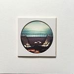 """""""Sesimbra Atlantico"""", pièce unique 10 x 10 cm, signée au dos, faite à la main par la photographe. Image choisie, découpée, recadrée, insérée derrière le hublot protecteur, comme une loupe sur la miniature, fixée au papier canson, avec un espace de méditation neutre autour du cercle de l'image, le tout sur un support carton plume d'un centimètre d'épaisseur. Le motif circulaire est aussi un hommage à l'écrivain poète portugais Fernando Pessoa qui portait des lunettes cerclées."""