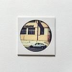 """""""Auto Industrial"""", pièce unique 10 x 10 cm, signée au dos, faite à la main par la photographe. Image choisie, découpée, recadrée, insérée derrière le hublot protecteur, comme une loupe sur la miniature, fixée au papier canson, avec un espace de méditation neutre autour du cercle de l'image, le tout sur un support carton plume d'un centimètre d'épaisseur. Le motif circulaire est aussi un hommage à l'écrivain poète portugais Fernando Pessoa qui portait des lunettes cerclées."""