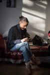 Jane Bouvier, founder of the association L'école au Présent, working for one of the Rom Families in their private space of the Squat in Marseille. Jane Bouvier, fondatrie de l'école au Présent, réglant un problème pour l'une des familles Roms dans leur espace privé dans le squat  à Marseille.