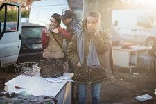 Jane Bouvier, founder of the association l'Ecole au présent , solving problems on the phone, and members of a Rom family outside  in a Squat in Marseille, former french army quarter. Jane Bouvier, fondatrice de l'école au présent, résolvant un problème par téléphone,  et des membres d'une famille  Rom dehors dans un squat de Marseille, ancienne carserne de L'armée française.