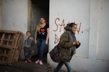 Jane Bouvier leaving the family outside a squat of Marseille, former french army quarter.  Jane Bouvier, après avoir salué la famille dehors, quitte un squat de Marseille, ancienne carserne de L'armée française.