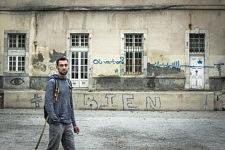 """Romain, militant de l'association ACARM09 pour l'accueil des migrants dans le Couserans, devant le graffiti """"Où va-t-on?"""", Saint-Girons, Ariège."""