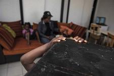 Les mains d'un enfant qui se tient près de sa famille dans un bureau désaffecté servant de logement provisoire, Ariège