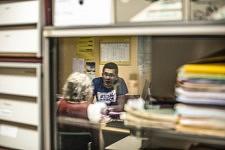 Dans les bureaux du Secours Populaire, Mireille, militante de Cent pour un Toit, aide un jeune migrant à remplir des papiers obligatoires afin qu'il puisse poursuivre son parcours vers l'obtention du statut de réfugié, Pamiers, Ariège