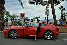Red sports Car and his young and rich driver on the Croisette; Cannes Film Festival. Voiture de sport rouge et son conducteur jeune et riche sur la Croisette, Festival de Cannes 2017.