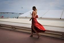 Woman wearing a red dress walking on the Croisette, Cannes, May 2017. Femme en robe rouge marchant sur la Croisette, Cannes, Mai 2017.