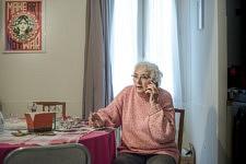 """Portrait de Mireille Becchio au téléphone dans sa salle à manger. Cette militante d'expérience de Cent pour Un Toit s'acharne à résoudre de nombreux problèmes par téléphone. C'est un trait commun à tous les aidants, bénévoles et militants qui passent leur vie dans leur voiture personnelle ou sur leur portable. Le cadre informel du quotidien le plus """"banal"""" de Mireille n'est pas sans rappeler fortuitement le cadre bien plus formel et lourd de sens de l'iconographie officielle du bureau d'Emmanuel Macron à l'Elysée depuis son élection avec l'affiche """"Make Art Not War"""" de l'artiste Shepard Fairey qui a repris la Marianne et ses symboles graphiques. Une des versions de cette oeuvre est visible en arrière plan des voeux présidentiels notamment et interroge ironiquement les voeux d'un président et la réalité des politiques mises en place."""