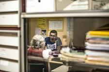 Mireille and Armen reflected in a computer screen, surrounded of piles of paper work, a symbol of the obstacle course for any migrant and helper.L'image de Mireille et Armen se reflète sur l'écran d'un ordinateur, encadré par des piles de dossiers, un symbole du parcours du combattant pour tout migrant et aidant.