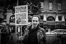 Man holding a sign saying he was violent towards against women before and that being concious of this, talking about it, fight against this is his story. Homme tenant un panneau disant qu'il a été l'auteur de violences faites aux femmes et qu'il lutte maintenant contre ça.