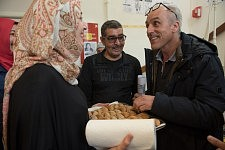 Philippe Poutou tasting the homemade food of a resident of the dermatological building occupied by families of migrants and the Dal, Hôpital de la Grave, Toulouse.