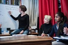 Refugees listening to the speaker while a french teacher is writing new words to know. Réfugiées écoutant l'intervenante pendant que la professeure de français écrits au tableau des nouveaux mots à connaître.