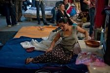 Public autour d'une jeune fille Rom sur son matelas pendant la Journée sur l'exclusion des Roms et contre le racisme d'état à la Maison de l'Arbre à Montreuil, septembre 2010.