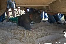 Marc Chambon, the new owner of the machine, repairing something under the combine harvester, Saint-Martin Cantalès, 2009. Marc Chambon, le nouveau propriétaire de la machine, entrain de réparer quelque chose sous la moissonneuse batteuse, Saint-Martin Cantalès, 2009.