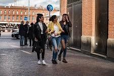 Three young trandy sisters walking of La Place du Capitole, Toulouse, February 2017. Trois soeurs, jeunes et branchées quittant la Place du Capitole vers les petites rues du centre, Toulouse, février 2017.