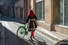 Young woman with red hair holding her green bike in a sunny street of Toulouse, December 2016. Jeune femme à cheveux rouge tenant son vélo vert dans une rue ensoleillée de Toulouse, Décembre 2016.