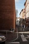 Young girl sitting on a march and man cycling in a street of the neighborhood Les Carmes in Toulouse, February 2017. Jeune fille assise sur une marche et un homme passant à vélo dans une rue du quartier des Carmes à Toulouse, Février 2017.