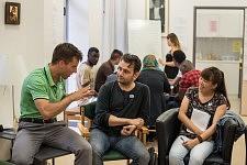 Deux participants et un enseignant pendant l'atelier de conversation en français chez JRS à Paris, juillet 2017.