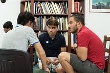 Trois participants de différentes nationalités faisant connaissance pendant l'atelier de conversation en français chez JRS à Paris, juillet 2017.